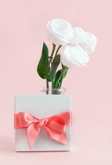 Fiocco regalo con fiocco e fiori bianchi su sfondo rosa chiaro si chiuda
