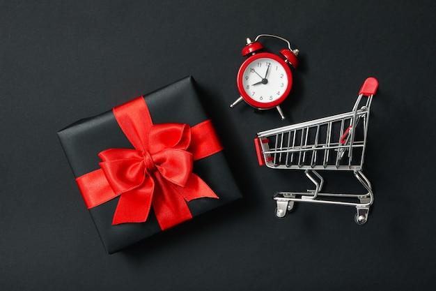 Confezione regalo, sveglia e carrello del negozio su fondo nero
