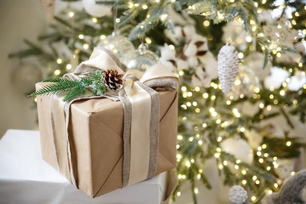 Regalo in scatola su sfondo di ghirlanda di natale e albero di capodanno