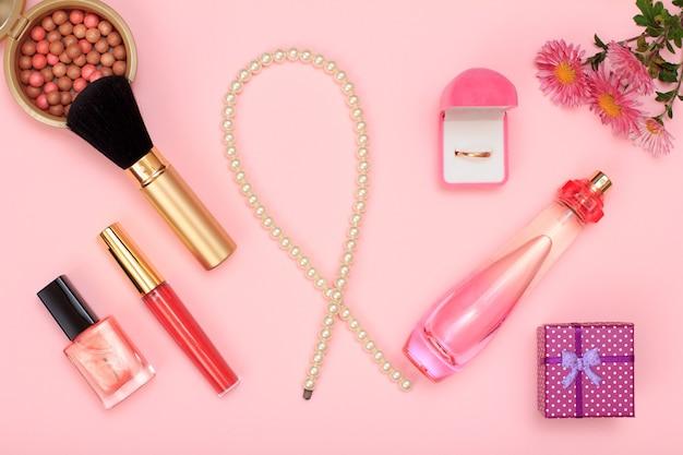 Confezione regalo, perline, bottiglia di profumo, smalto per unghie e anello dorato in scatola, polvere su sfondo rosa. cosmetici e accessori donna. vista dall'alto.