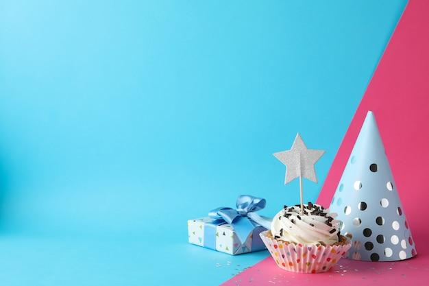Confezione regalo, cappello compleanno e cupcake su uno sfondo di due toni, spazio per il testo