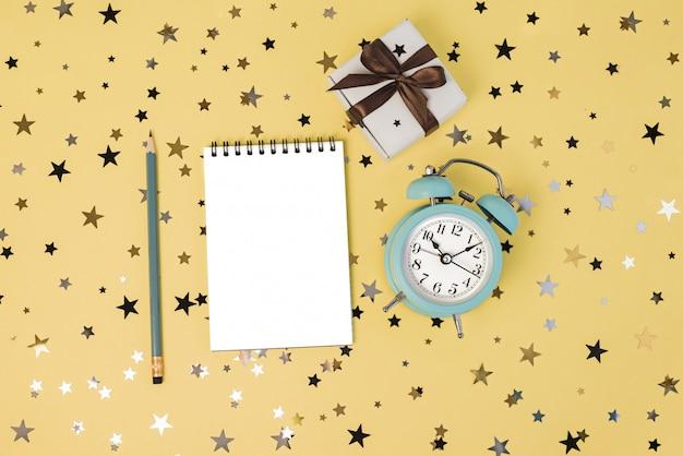 Contenitore di regalo, orologio blu e taccuino pulito con la matita sulla tavola gialla con i coriandoli delle stelle.