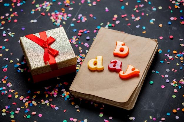 Confezione regalo e libro con coriandoli su un tavolo