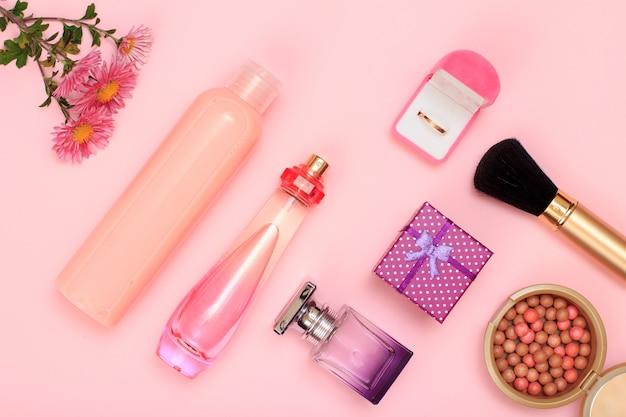 Confezione regalo, bottiglie di profumo, shampoo e anello dorato in scatola, polvere con pennello su sfondo rosa. cosmetici e accessori donna. vista dall'alto.