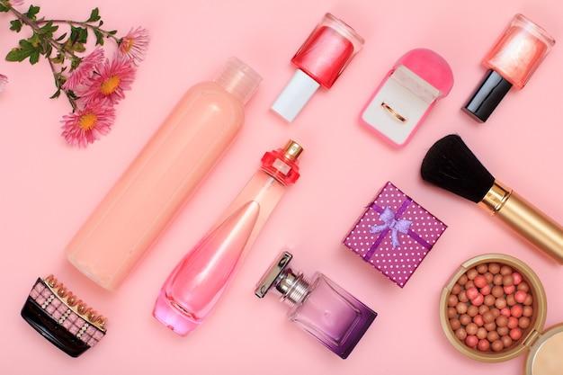 Confezione regalo, flaconi di profumo e shampoo, fermacapelli, anello dorato in scatola, smalto per unghie, polvere con pennello su sfondo rosa. cosmetici e accessori donna. vista dall'alto.
