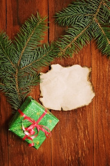 Confezione regalo e rami di albero di natale, fondo in legno