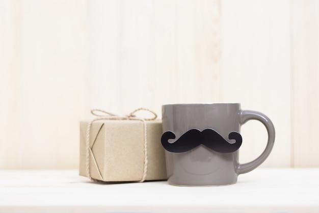 Contenitore di regalo, tazza di caffè, baffi di carta su fondo di legno con lo spazio della copia. buona festa del papà.