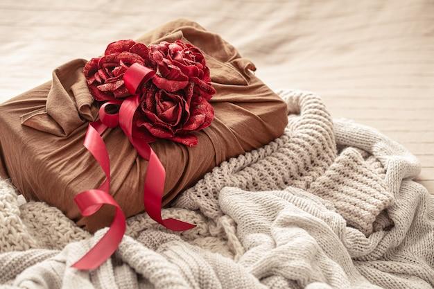 Confezione regalo decorata con nastri e rose decorative su articoli in maglia. confezione regalo originale per san valentino.