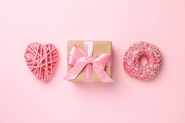 Confezione regalo, ciambella e cuore su sfondo rosa, spazio per il testo