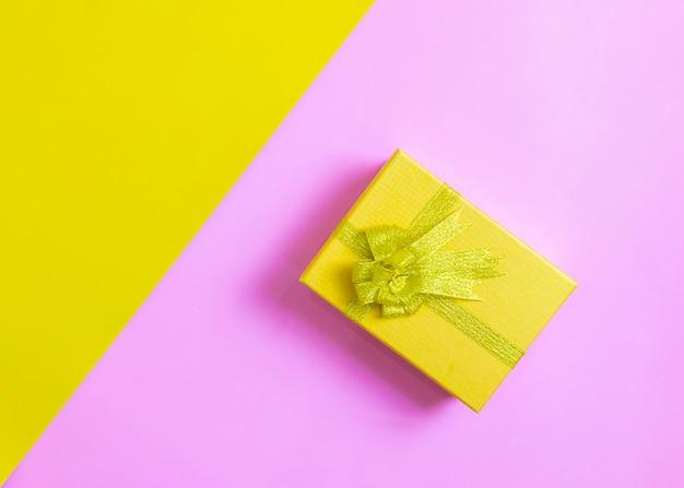 Contenitore di regalo sullo sfondo giallo e rosa di giorno di festival