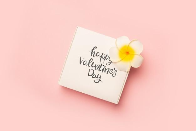Confezione regalo e fiori su una superficie rosa pastello
