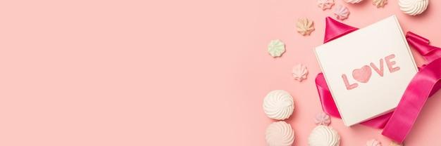 Confezione regalo e caramelle regalo, marshmallow e meringhe su una superficie rosa pastello