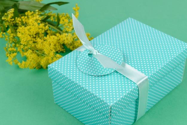 Confezione regalo su verde con fiore giallo.