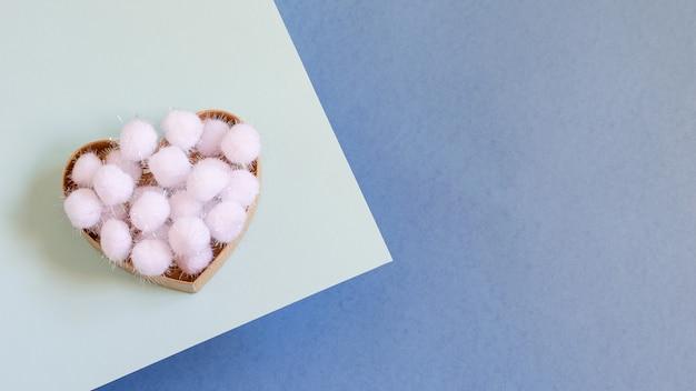 Scatola regalo a forma di cuore con fiocchi di neve decorativi soffici bianchi su sfondo blu bicolore.