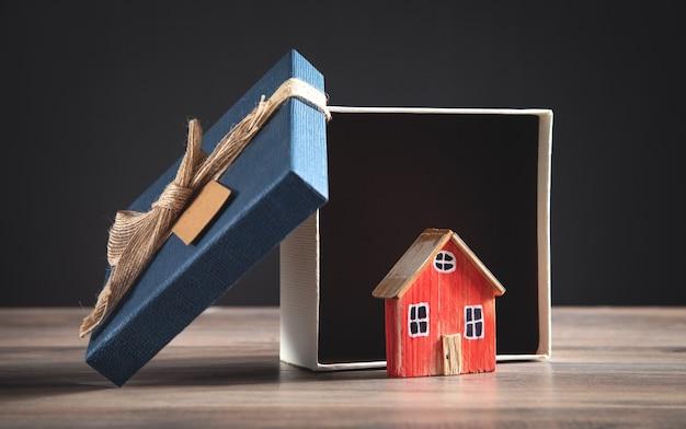 Confezione regalo e modello di casa sul tavolo di legno.