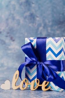 Il contenitore di regalo e l'iscrizione amano su fondo blu. concetto di regali per gli uomini.