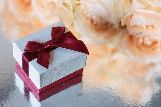 La confezione regalo si trova su una superficie argentata sullo sfondo di rose gialle.