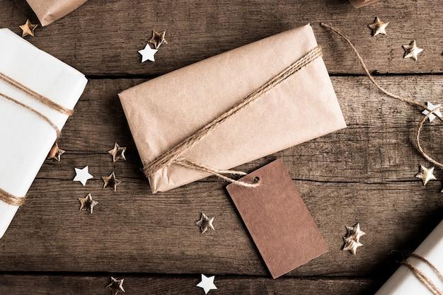 Confezione regalo in carta kraft con etichetta grande per spazio copia su sfondo scuro vista dall'alto rustico welcome