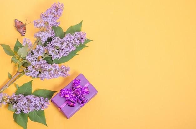 Confezione regalo e fiori lilla su sfondo giallo con spazio di copia