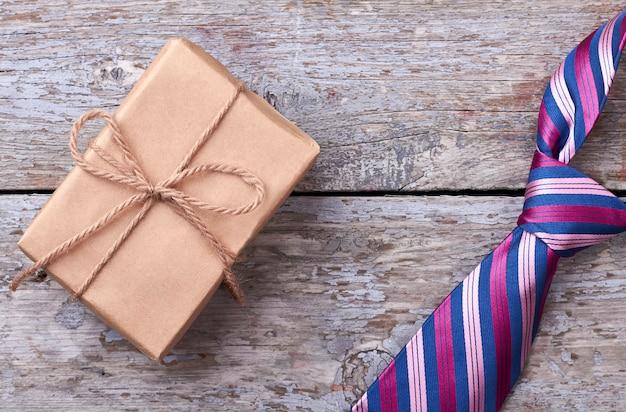 Confezione regalo vicino alla cravatta a righe. legare su una superficie di legno. come scegliere un regalo.