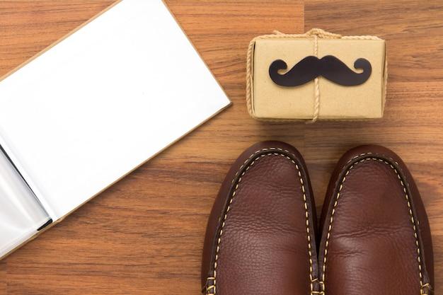 Contenitore di regalo, baffi di carta, scarpe, fotolibro su fondo di legno con lo spazio della copia. buona festa del papà.