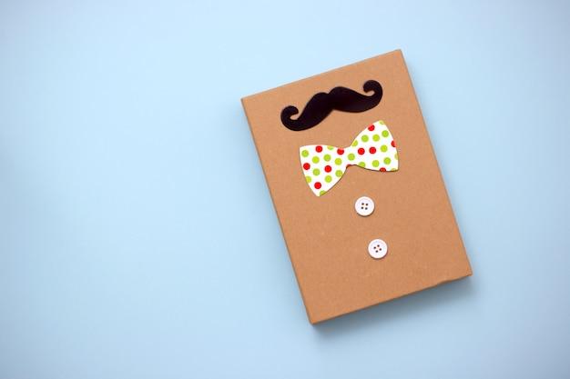 Confezione regalo, baffi di carta, cravatta su sfondo blu pastello con spazio di copia. buona festa del papà.