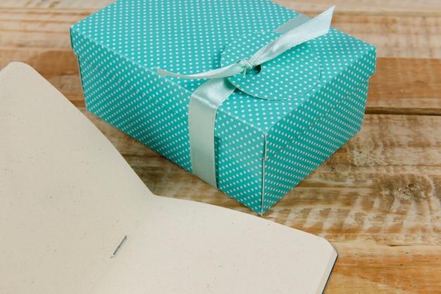 Confezione regalo accanto al blocco note di carta su legno rustico.
