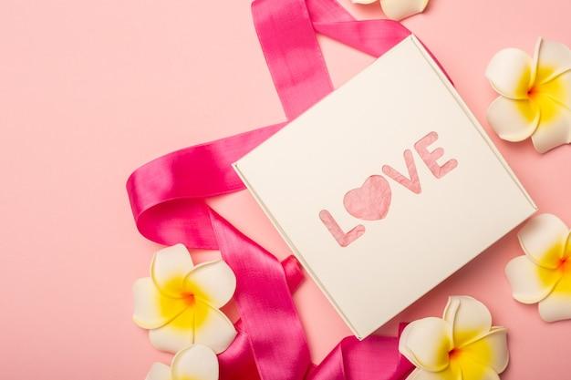 Confezione regalo, nastro rosa e fiori su una superficie rosa pastello