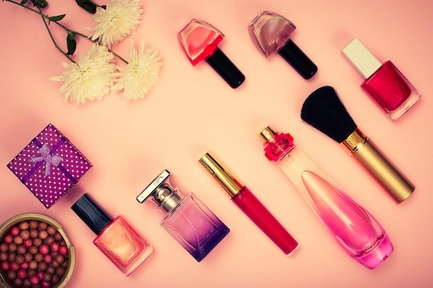 Confezione regalo, polvere, smalto per unghie, bottiglie di profumo, rossetto, pennello e fiori su sfondo rosa. cosmetici e accessori donna. vista dall'alto. tonificazione del colore.