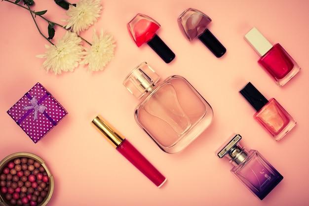 Confezione regalo, polvere, smalto per unghie, bottiglie di profumo, rossetto e fiori su sfondo rosa. cosmetici e accessori donna. vista dall'alto. tonificazione del colore.