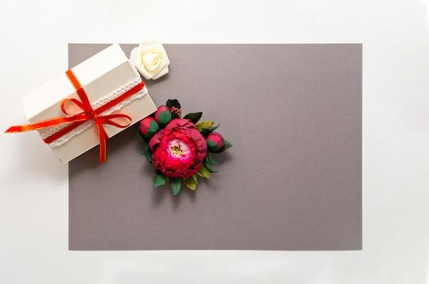 Confezione regalo presente decorazioni flatlay. vista superiore dei fiori bianchi di rosa del nastro rosso del regalo.