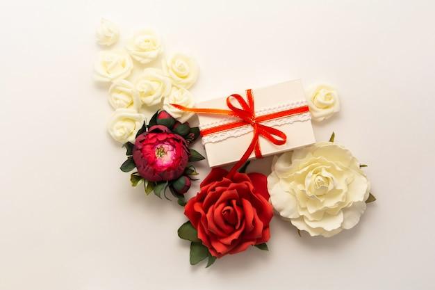 Confezione regalo presente decorazioni flatlay. vista superiore del regalo, nastro rosso, fiori di rossi carmini