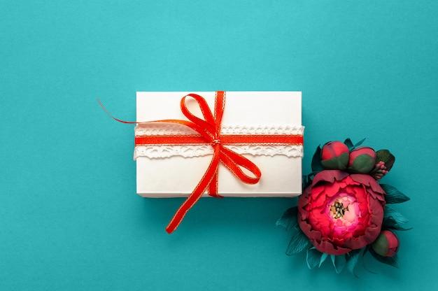 Confezione regalo presente decorazioni flatlay. vista superiore dei fiori rosa del nastro bianco del regalo.