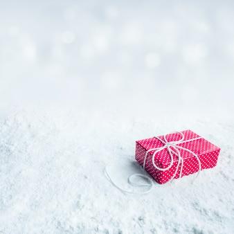 Confezione regalo, presente su sfondo di neve. per concetti di natale o capodanno, idee di celebrazione