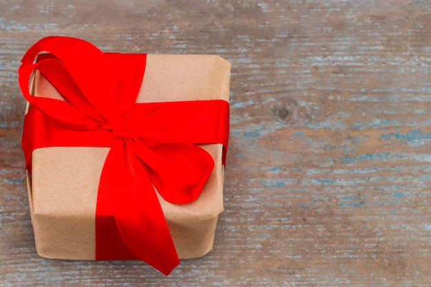 Confezione regalo presente con nastro fiocco rosso e carta da imballaggio kraft marrone su fondo in legno, la vista dall'alto con spazio copia.