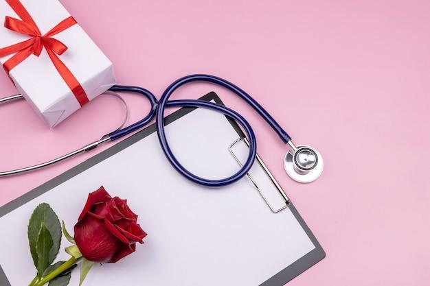 Confezione regalo tavoletta di carta rosa rossa e stetoscopio