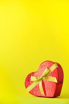 Confezione regalo a forma di cuore rosso su sfondo giallo. san valentino. appuntamento romantico e il concetto di amore.