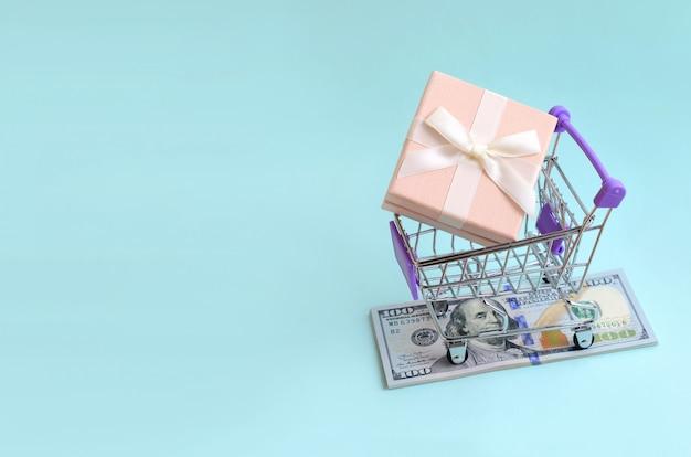 Il contenitore di regalo in un piccolo carrello di acquisto si trova sulle banconote in dollari su blu-chiaro