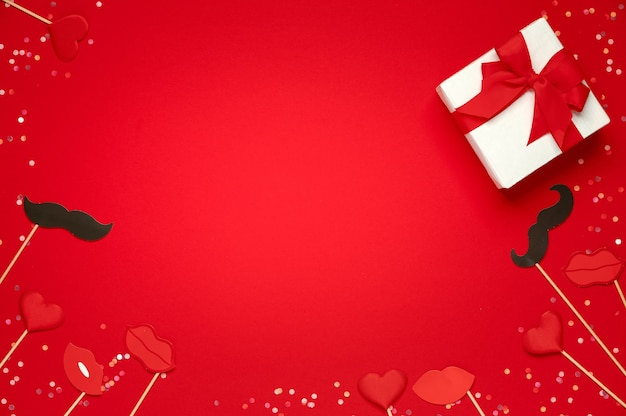 Confezione regalo e labbra morbide cuori e baffi di carta su sfondo rosso. modello di san valentino