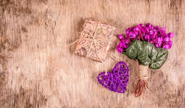Confezione regalo e fiori primaverili, violette delicate e cuore.