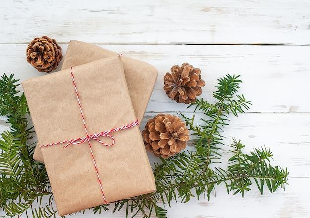 Confezione regalo, rami di abete rosso e coni su superficie di legno bianca