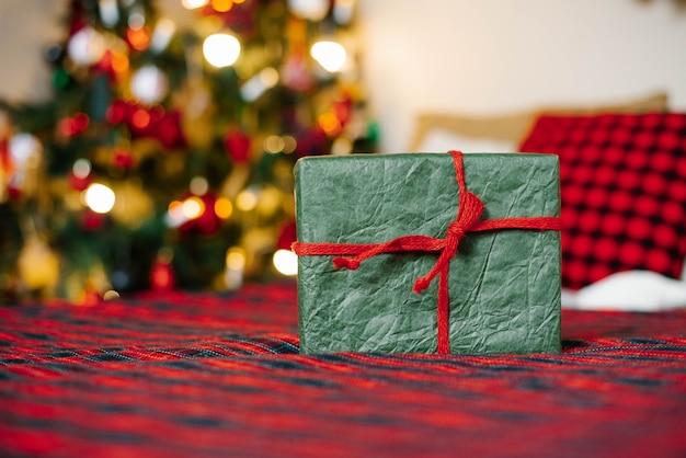 Confezione regalo legata con un nastro rosso sopra le luci di natale