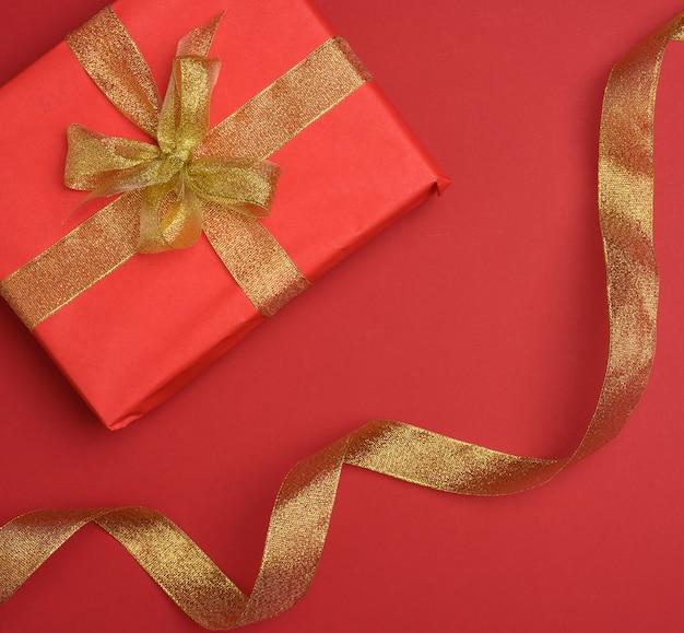 Confezione regalo legata con nastro di seta su fondo rosso, vista dall'alto. sfondo festivo