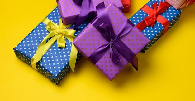 Confezione regalo legata con nastro di seta su sfondo giallo, vista dall'alto. sfondo festivo
