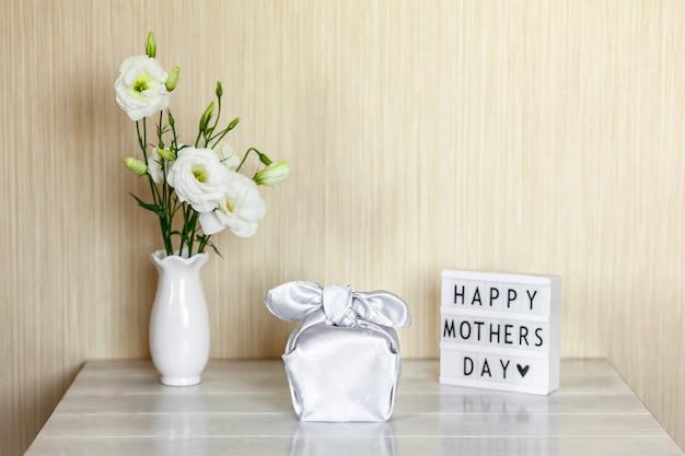 Confezione regalo trendy avvolta in tessuto di seta con tecnica furoshiki, light box con scritta happy mother's day, fiori bianchi eustoma o lisianthus in vaso su tavola di legno. zero concetto di vita dei rifiuti.