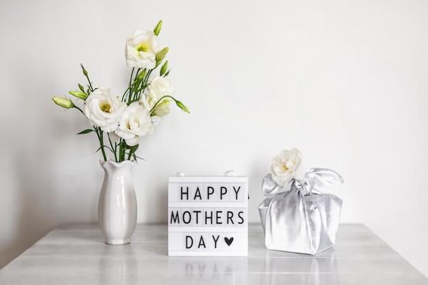 Confezione regalo trendy avvolta in tessuto di seta con tecnica furoshiki, light box con scritta happy mother's day
