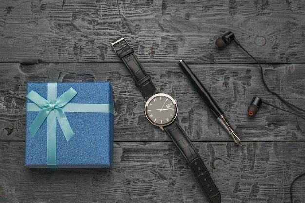 Confezione regalo, orologio, penna stilografica e cuffie su fondo in legno. un regalo per un uomo.