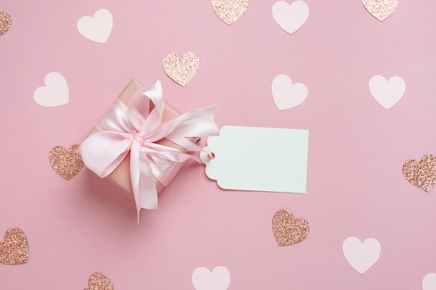 Confezione regalo con tag regalo vuoto su sfondo rosa pastello con molti cuori. composizione di san valentino. vista dall'alto, piatto.