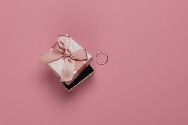 Confezione regalo con fiocco e anello in oro su sfondo rosa pastello. concetto di matrimonio. gioielleria. vista dall'alto. lay piatto