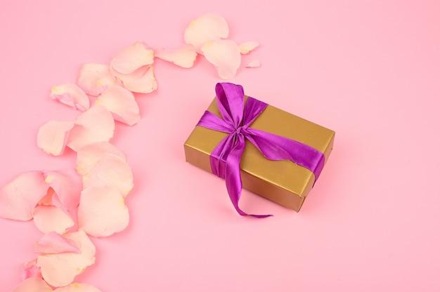 Contenitore di regalo con l'arco su fondo di carta rosa. biglietto di auguri per compleanno, festa della mamma o san valentino.